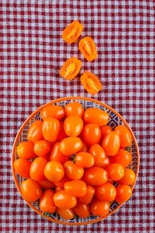 ピクニック布のスライストップビューでプレートのトマト