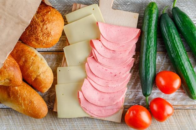 Помидоры с хлебом, сыром, колбасой, огурцами плоско уложить на деревянный стол