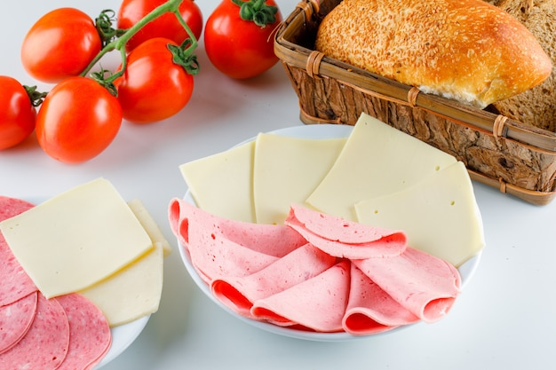 Помидоры с хлебом, сыром, колбасой высокого угла зрения