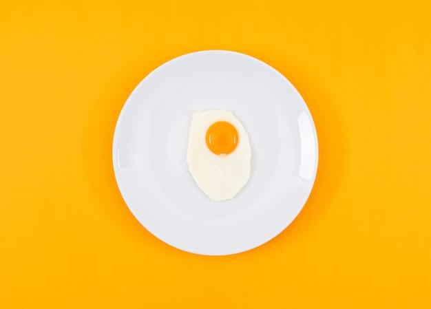Вид сверху жареного яйца на белой тарелке и на желтой горизонтальной поверхности
