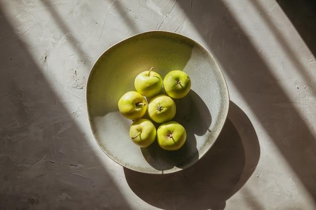 織り目加工のテーブルの上の皿に上面の緑のリンゴ。横型