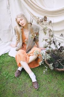 オレンジ色のドレスと地面に座っていると庭で見ているジャケットで美しい女性。
