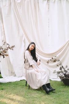 Милая женщина сидя на стуле и смотря в саде