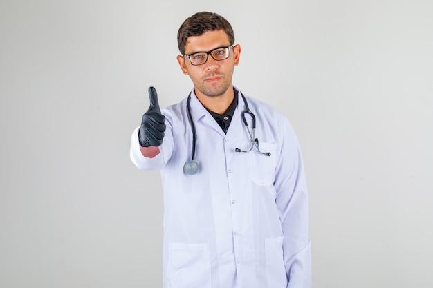 Доктор в медицинском белом халате делает большой палец вверх знак и выглядит счастливым