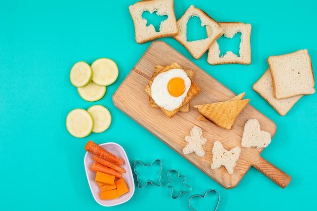 Вид сверху жареного яйца с тостами и овощами на синей горизонтальной поверхности