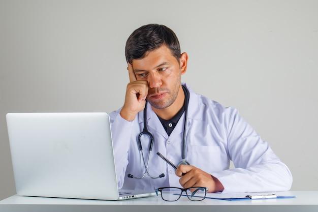 Доктор в белом халате, стетоскоп сидит и смотрит на ноутбук и смотрит осторожно