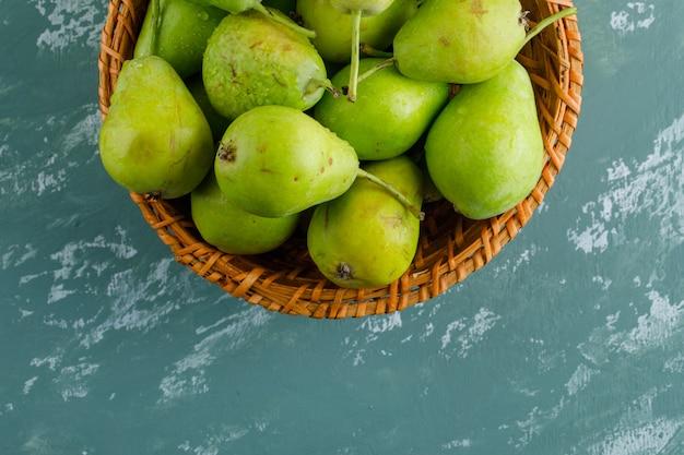 しっくいの表面に平らなバスケットの緑の梨を置く