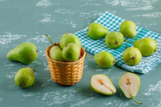漆喰とキッチンタオルの表面にバスケットの緑の梨、高角度のビュー。