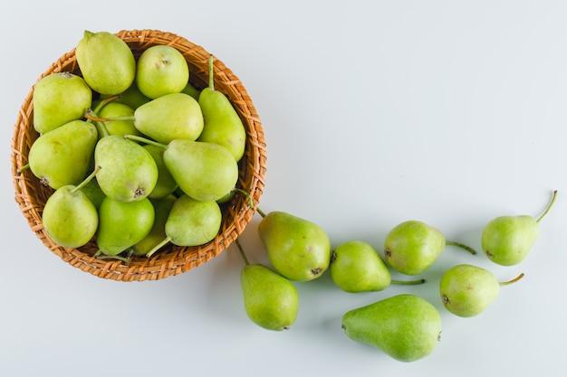 白いテーブルの上のバスケットに緑色の洋ナシ