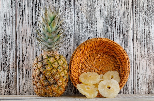 木の表面にバスケットに新鮮なパイナップルとパイナップルを乾燥