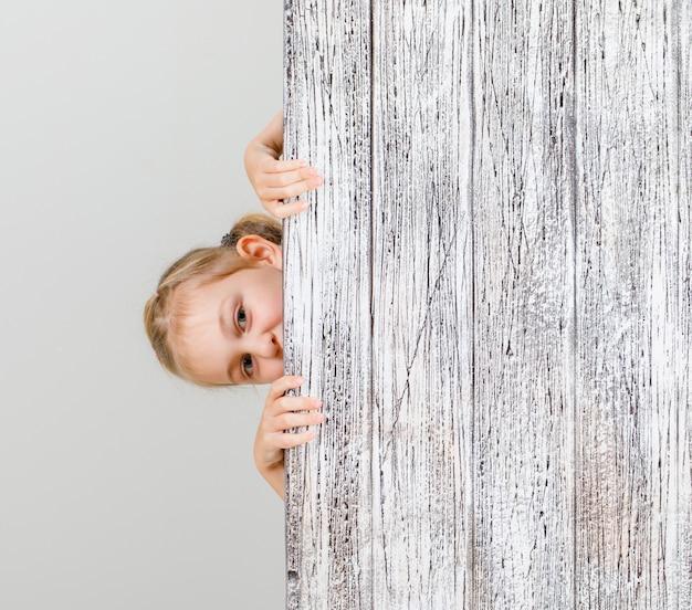 木の板の後ろでこっそり見つめて少女。