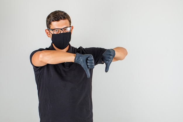 男性医師が黒のポロシャツに親指を表示し、不満を探して