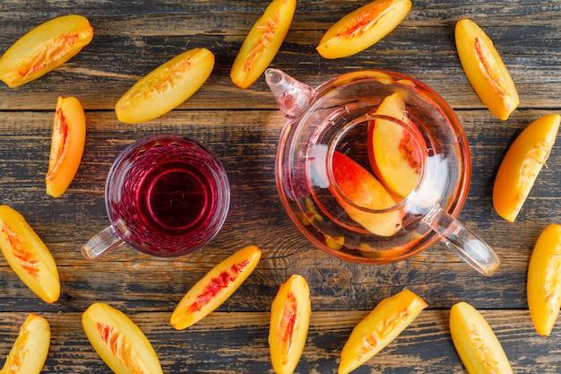 木製のテーブルの上に置くフラット冷たい飲み物とネクタリン