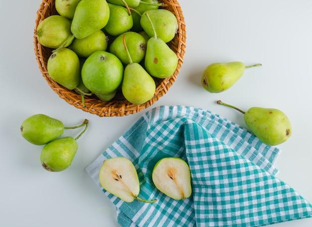 白とキッチンタオルテーブルの上のバスケットの梨