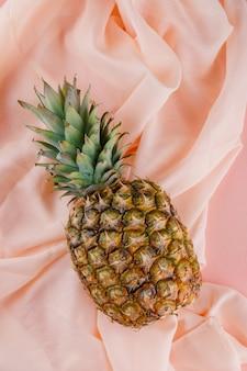 Ананас на розовой и текстильной поверхности