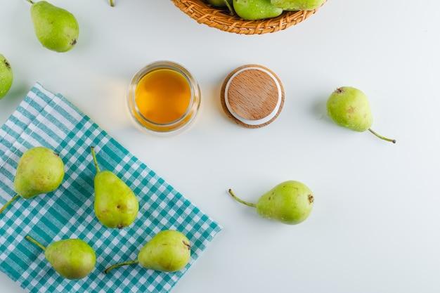 白とキッチンタオルの上蜂蜜上面とバスケットの梨
