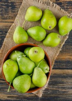 ボウルの梨は木製と袋の一部の上に置く