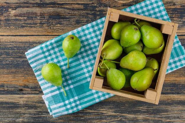 Груши в коробке на предпосылке деревянных и кухонного полотенца. вид сверху.