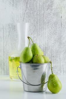 白と汚れた壁にハーブドリンクの側面図とミニバケツの梨