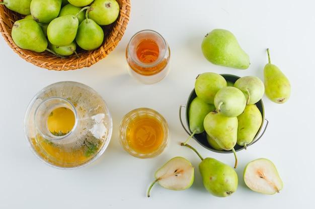 バスケットとフラットバケツで梨の白いテーブルの上に置く