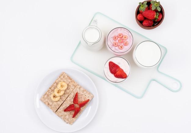 Вид сверху йогурта с тостами на белой горизонтальной поверхности