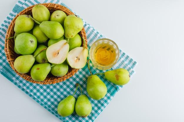 白とキッチンタオルテーブルの上のバスケットに飲み物と梨