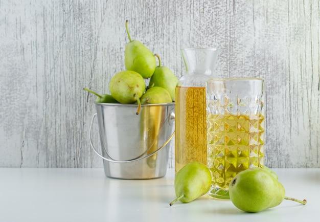 白と汚れた壁、側面図のミニバケツで飲み物と梨。