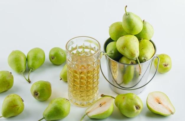白い表面、高角度のビュー上のミニバケツで飲み物と梨。