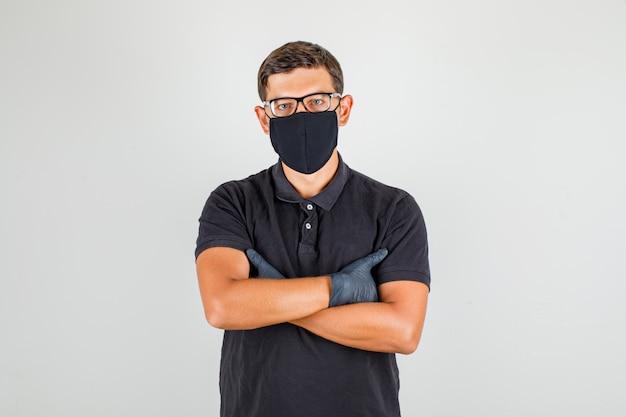 腕を交差し、カメラ目線と自信を持って探している黒のポロシャツの若い医者