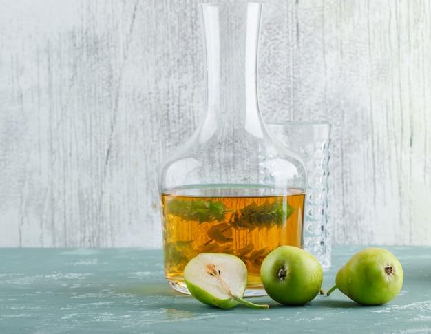 ハーブの飲み物、石膏と汚れた壁、側面図の空のグラスと梨。