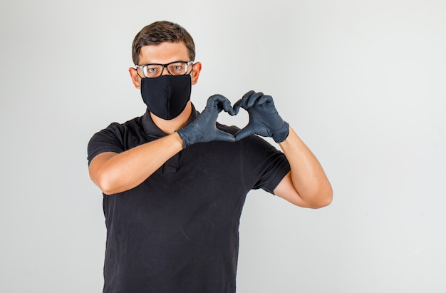 若い医者が黒いポロシャツで心のジェスチャーを作ると喜んで