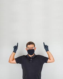 若い医者は黒のポロシャツで指を上向き