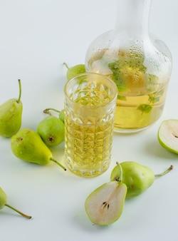 白い表面、高角度のビューでハーブの飲み物と梨。