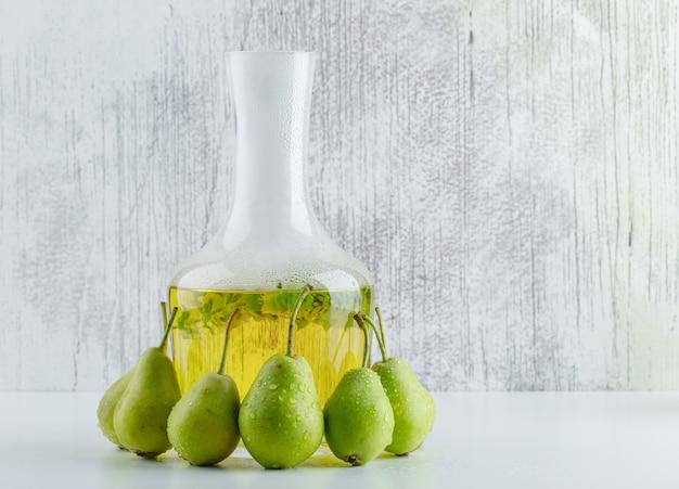 白と汚れた壁にハーブの飲み物の側面図と梨