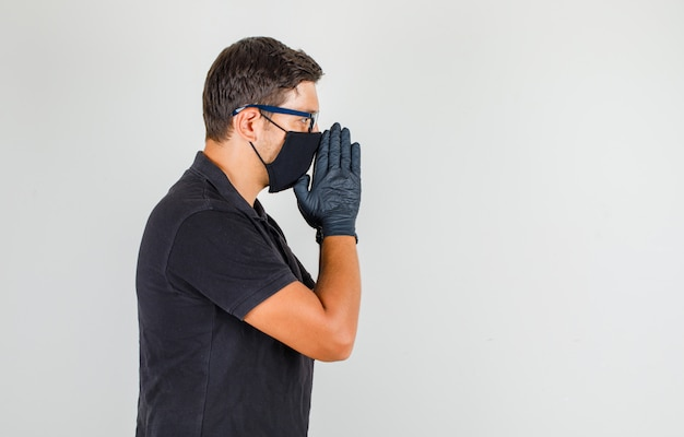 若い医者が黒のポロシャツで祈り、心配そうに見えて