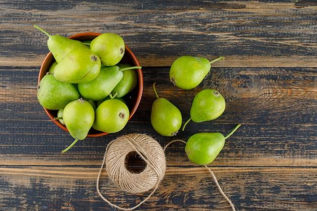 木製のテーブルの上にボウルにスレッドボールと梨が横たわっていた。