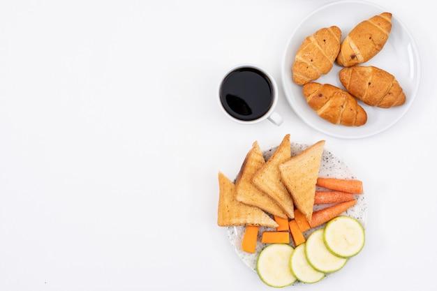 クロワッサン、コーンフレーク、白い背景の水平方向にコピースペースでコーヒーと朝食の平面図