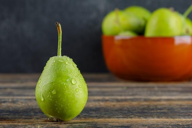 木製と灰色のテーブルのボウルサイドビューで熟した梨