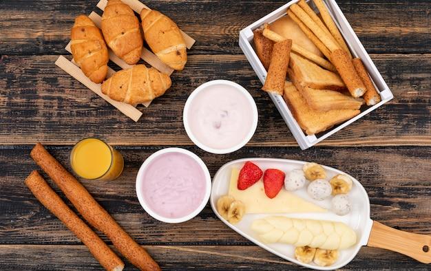 トースト、クロワッサン、ヨーグルト、チーズ、暗い木製の表面水平に朝食の平面図