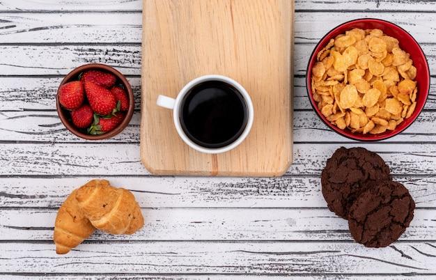 クッキーとクロワッサン、白い木製の表面の水平にイチゴとコーンフレークとコーヒーのトップビュー