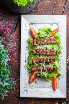 新鮮なレタス、パルメザンチーズ、揚げクルトン、ローストビーフのトップビューシーザーサラダ
