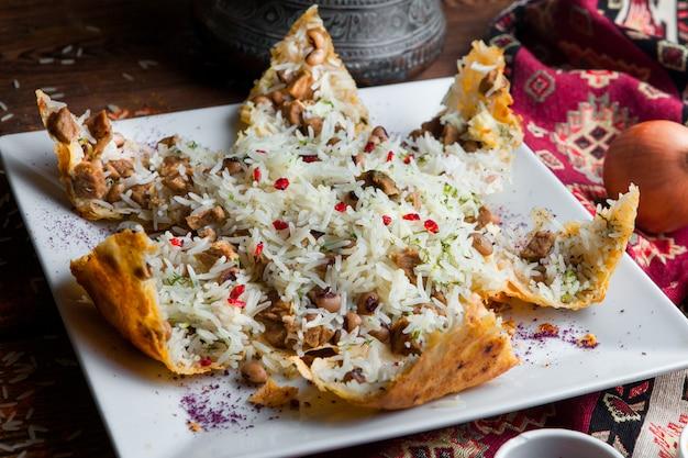 肉、豆、スパイスが入ったピタのクローズアップピラフ。暗い木製のテーブルの水平に伝統的な東洋料理