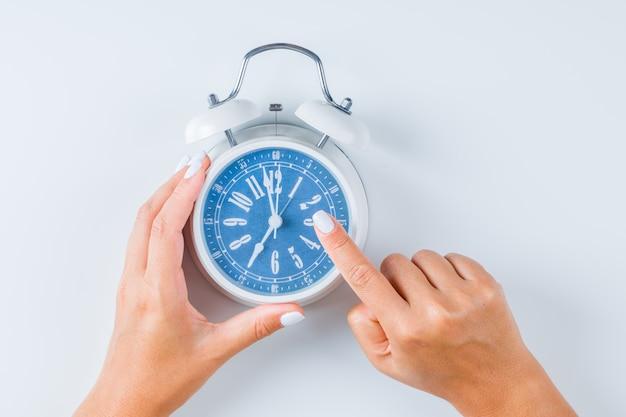 目覚まし時計を指している指