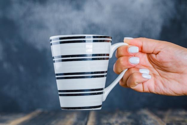 Рука держит чашку