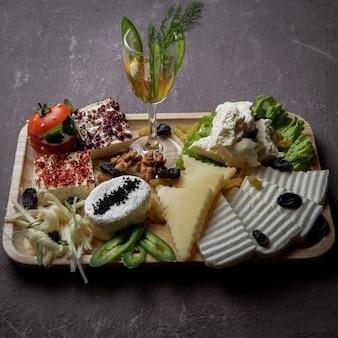 Вид сбоку сырная нарезка разных видов сыра, орехов, изюма, томатов на темной цементной поверхности