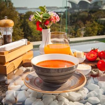 トマトのサイドビュートマトスープ、ストーンサットシーサイドレストランで飾られたガラステーブルの上のジュース