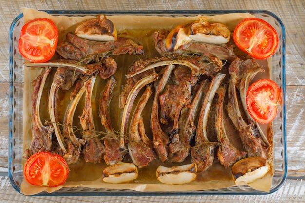 木製のテーブルのガラスのグラタン皿にリンゴとトマトのグリル肉、フラットが横たわっていた。