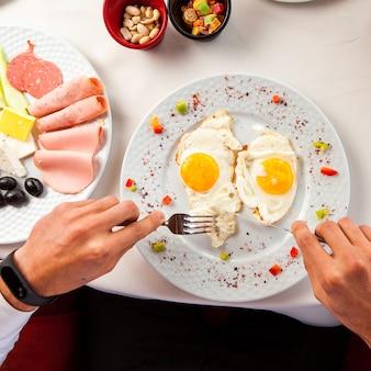 白いテーブルクロス、オリーブ、チーズ、ハム、ナッツ、フォークとナイフの朝食を持つ男の砂糖漬けの果物の手でテーブルの上のテーブルに目玉焼き