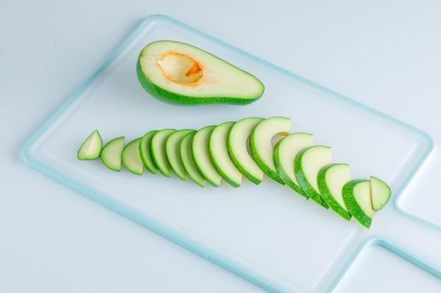 Авокадо ломтики сверху на белом и разделочная доска