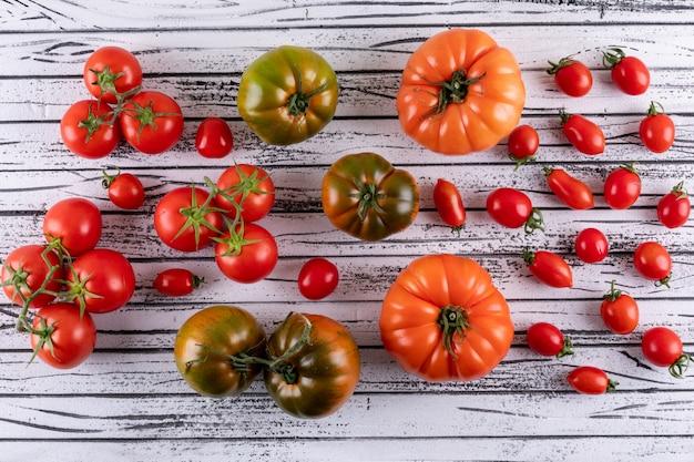 Зеленые оранжевые помидоры и ветви помидоров черри на белом деревянном